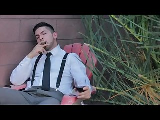Handsome classy man smoking cigar in his suspenders suit tie clean cut male