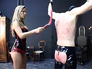 Latex mistress lets her dog slave out of the cage to be whipped