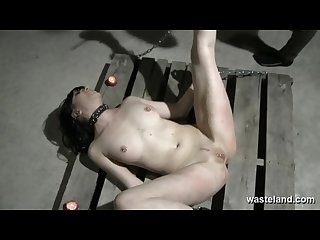 Brunette sex slave Chained to pallet on the dungeon floor and caned
