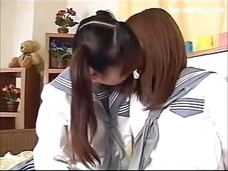 Young schoolgirls in uniform kissing passionately on the bed
