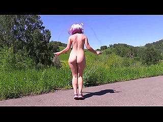 Sexy nudist in a public place jumps on a jump rope outdoors and shakes a big butt...