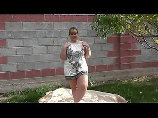 Anal masturbation in the garden outdoors, a bbw is entertained with a sex toy and shakes a..