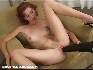 Petite redhead Evelyn gapes herself with a brutal dildo