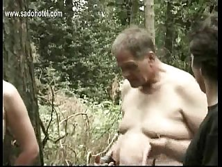 Horny slave tied to tree gets pulled on her beautiful tits and gets hit on her cunt with a stick