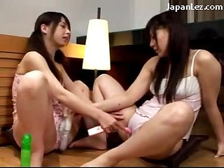 2 young schoolgirls in lingerie sticking toys to each other pussies on the floor